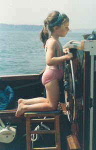 Vicky as a child steering a boat
